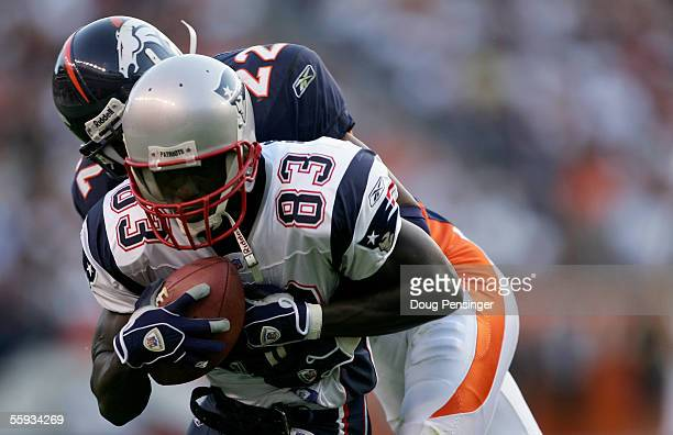 Deion Branch of the New England Patriots makes a pass reception for a first down and is taken down by Domonique Foxworth of the Denver Broncos as the...