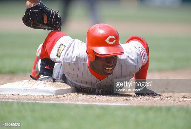 Deion Sanders of the Cincinnati Reds dives back into first base beating the tag of Dave Martinez of the San Francisco Giants during an Major League...