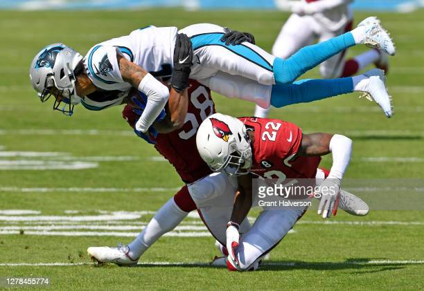 Deionte Thompson and Jordan Hicks of the Arizona Cardinals tackle Robby Anderson of the Carolina Panthers during the first quarter of their game at...