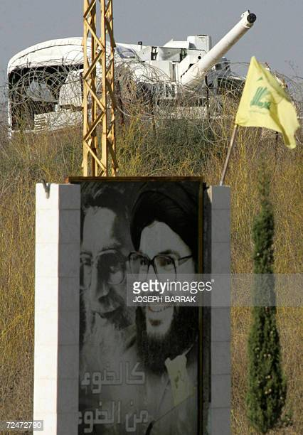 A Hezbollah flag flutters over a poster of its leader Hassan Nassrallah and Iran's supreme leader Ayatollah Ali Khamenei as French soldiers atop a...