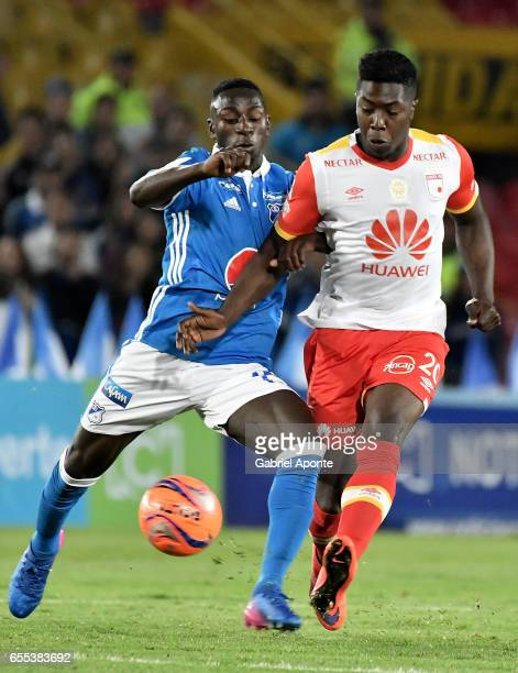 Deiver Machado of Millonarios struggles for the ball with Jose Adolfo Valencia of Santa Fe during the match between Millonarios and Independiente...