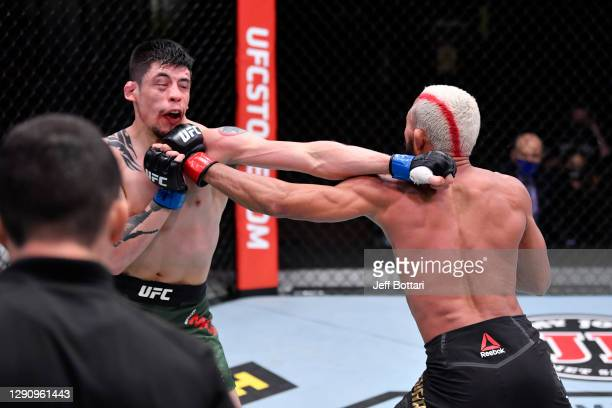 Deiveson Figueiredo of Brazil and Brandon Moreno of Mexico exchange punches in their flyweight championship bout during the UFC 256 event at UFC APEX...