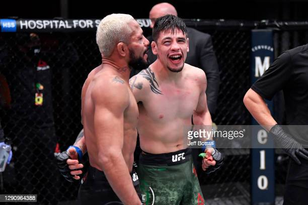 Deiveson Figueiredo of Brazil and Brandon Moreno of Mexico react after their flyweight championship bout during the UFC 256 event at UFC APEX on...