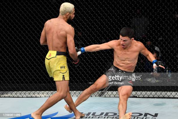 Deiveson Figueiredo of Brazil drops Joseph Benavidez with a punch in their UFC flyweight championship bout during the UFC Fight Night event inside...