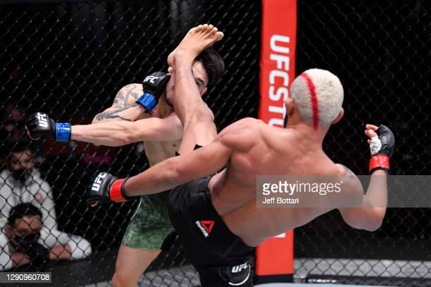 Deiveson Figueiredo of Brazil kicks Brandon Moreno of Mexico in their flyweight championship bout during the UFC 256 event at UFC APEX on December...