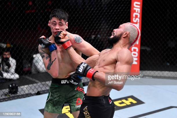 Deiveson Figueiredo of Brazil punches Brandon Moreno of Mexico in their flyweight championship bout during the UFC 256 event at UFC APEX on December...