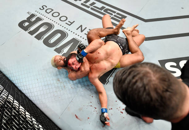 Deiveson Figueiredo of Brazil secures a rear choke submission against Joseph Benavidez in their UFC flyweight championship bout during the UFC Fight...