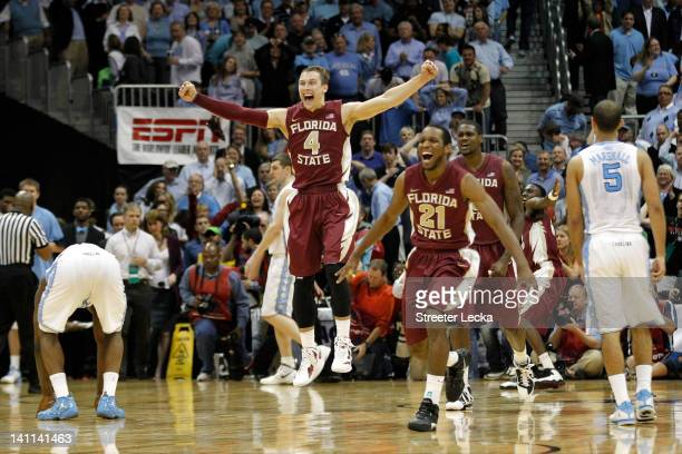 Deividas Dulkys and Michael Snaer of the Florida State Seminoles celebrate on court after they won 8582 against the North Carolina Tar Heels during...
