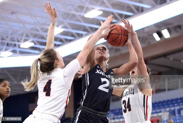 Deja Ross of the Xavier Musketeers attempts to overcome Isabella Posset and Holly Forbes of the Robert Morris Colonials during the second half at the...