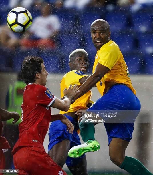 Dejan Jakovic of Canada fights for the ball with Arnold Abelinti and Sloan Privat of French Guiana during their Concacaf Gold Cup match at Red Bull...