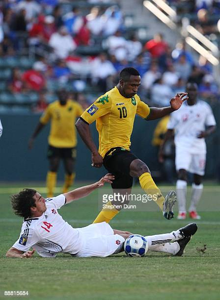 Dejan Jakovic of Canada slides to steel the ball from Ricardo Fuller of Jamaica during the 2009 CONCACAF Gold Cup at The Home Depot Center on July 3...