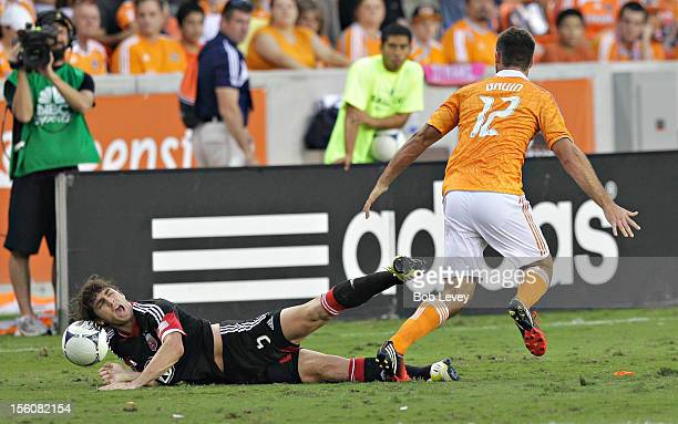 Dejan Jakovic of the DC United is tripped up by Will Bruin of the Houston Dynamo in the second half during Leg 1 of the MLS Eastern Conference...