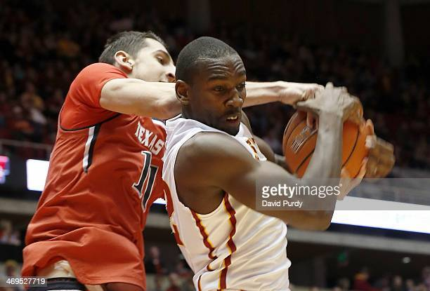 Dejan Kravic of the Texas Tech Red Raiders reaches over the back of Dustin Hogue of the Iowa State Cyclones as he pulls in a rebound in the first...