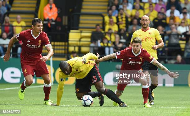 Dejan Lovren and Alberto Moreno of Liverpool with Stefano Okaka of Watford during the Premier League match between Watford and Liverpool at Vicarage...