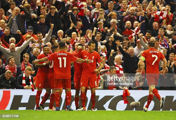 Dejan Lovren celebrates with team mates and fans as Adam Lallana of Liverpool scores their third goal during the UEFA Europa League semi final second...