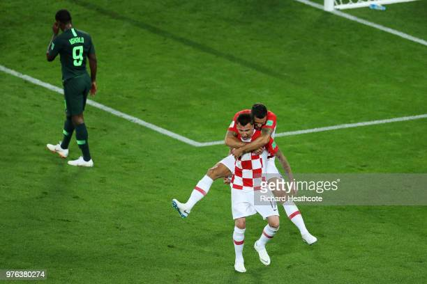 Dejan Lovren jumps on the back of Mario Mandzukic of Croatia as they celebrate after Oghenekaro Etebo of Nigeria scored an own goal as Odion Ighalo...