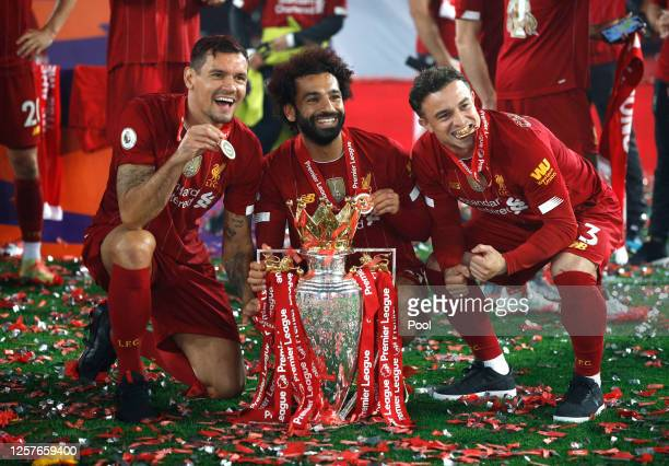 Dejan Lovren, Mohamed Salah and Xherdan Shaqiri of Liverpool celebrate with The Premier League trophy following the Premier League match between...