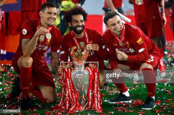 Dejan Lovren Mohamed Salah and Xherdan Shaqiri of Liverpool celebrate with The Premier League trophy following the Premier League match between...