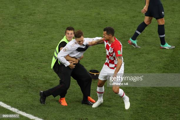 Dejan Lovren of Croatia confronts a pitch invader during the 2018 FIFA World Cup Final between France and Croatia at Luzhniki Stadium on July 15 2018...