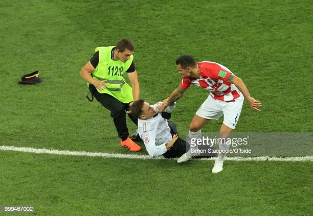 Dejan Lovren of Croatia grabs a pitch invader during the 2018 FIFA World Cup Russia Final between France and Croatia at the Luzhniki Stadium on July...