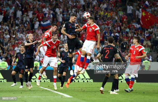 Dejan Lovren of Croatia wins a header over Roman Zobnin of Russia during the 2018 FIFA World Cup Russia Quarter Final match between Russia and...