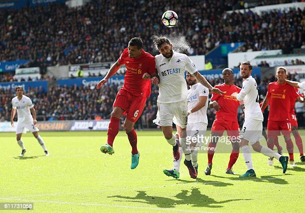 Dejan Lovren of Liverpool and Jordi Amat of Swansea City battle for possession in the air during the Premier League match between Swansea City and...