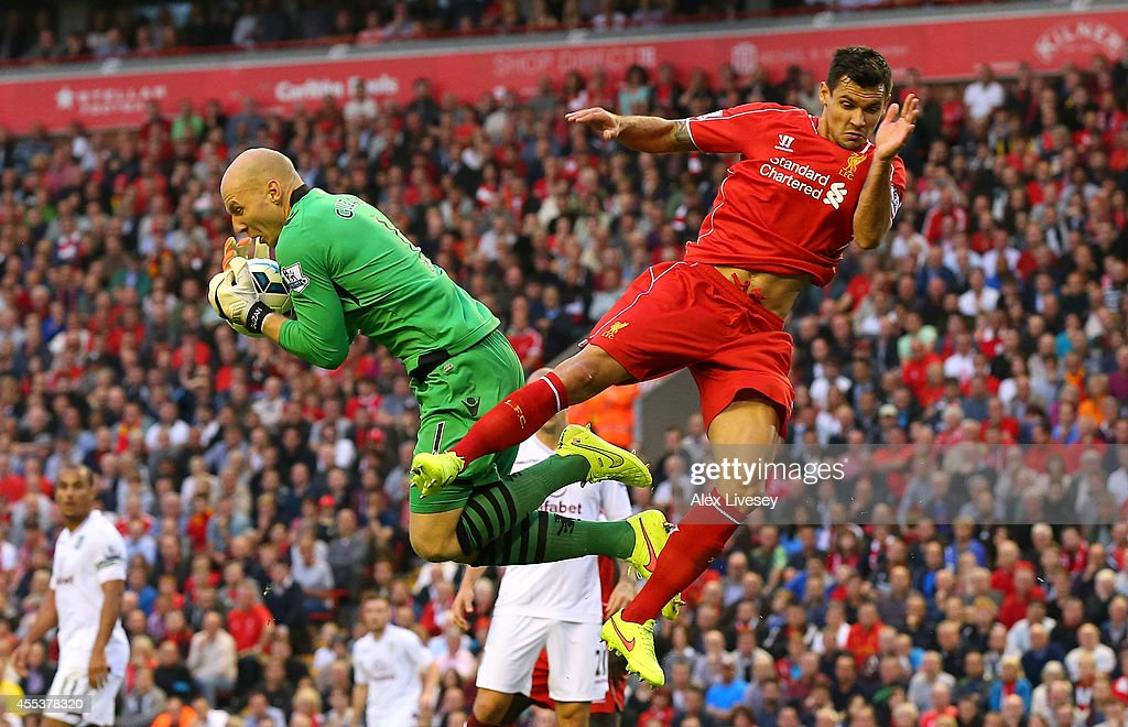 Dejan Lovren of Liverpool challenges Brad Guzan of Aston Villa during the Barclays Premier League match between Liverpool and Aston Villa at Anfield on September 13, 2014 in Liverpool, England.
