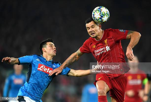 Dejan Lovren of Liverpool heads the ball clear as he is put under pressure by Hirving Lozano of Napoli during the UEFA Champions League group E match...