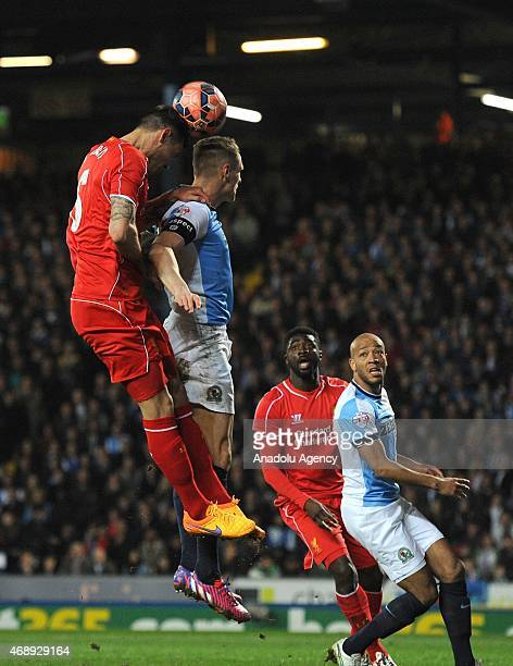 Dejan Lovren of Liverpool in action against Matthew Kilgallon of Blackburn Rovers during the FA Cup Quarter Final Replay match between Blackburn...