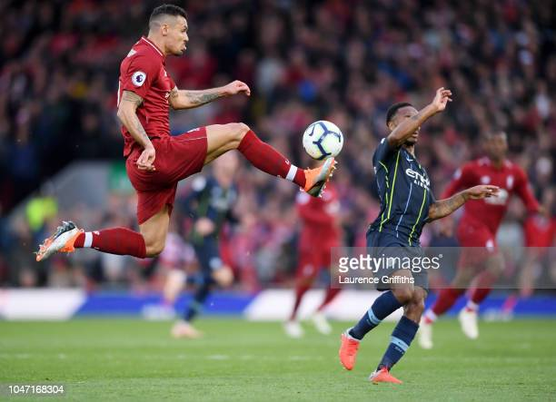Dejan Lovren of Liverpool jumps for the ball under pressure from Raheem Sterling of Manchester City during the Premier League match between Liverpool...