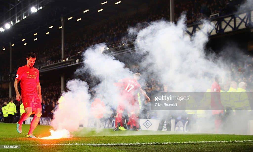 Dejan Lovren of Liverpool removes a flare from the pitch as Sadio Mane of Liverpool scores their first goal during the Premier League match between Everton and Liverpool at Goodison Park on December 19, 2016 in Liverpool, England.