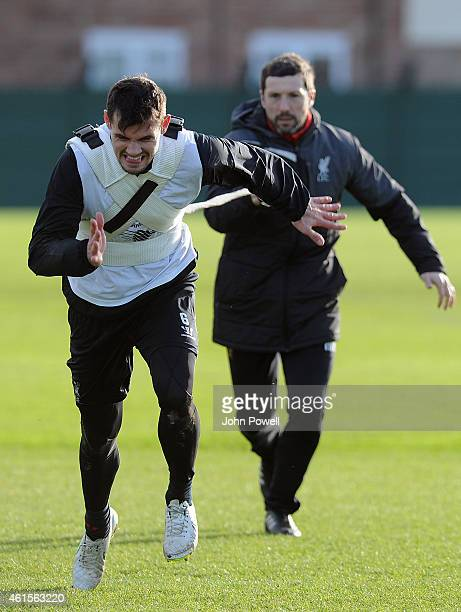 Dejan Lovren of Liverpool with Ryland Morgans head of fitness in action during a training session at Melwood Training Ground on January 15 2015 in...