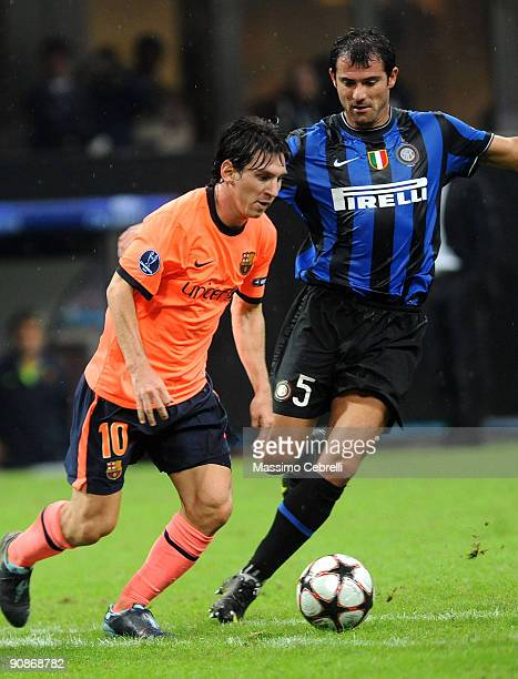 Dejan Stankovic of FC Inter Milan and Lionel Andres Messi of FC Barcelona challenge for the ball during the UEFA Champions League Group F match...