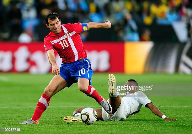 Dejan Stankovic of Serbia rides the tackle by Andrew Ayew of Ghana during the 2010 FIFA World Cup South Africa Group D match between Serbia and Ghana...