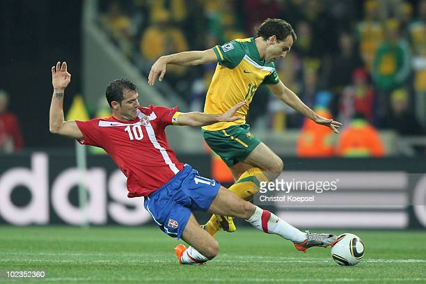 Dejan Stankovic of Serbia tackles Richard Garcia of Australia during the 2010 FIFA World Cup South Africa Group D match between Australia and Serbia...