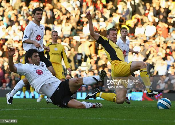 Dejan Stefanovic of Fulham and Steve Howard of Derby County stretch for the ball during the Barclays Premier League match between Fulham and Derby...