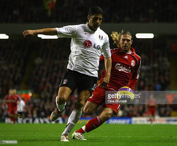 Dejan Stefanovic of Fulham battles for the ball with Andriy Voronin of Liverpool during the Barclays Premier League match between Liverpool and...