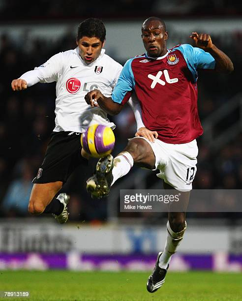 Dejan Stefanovic of Fulham challenges Carlton Cole of West Ham United during the Barclays Premier League match between West Ham United and Fulham at...