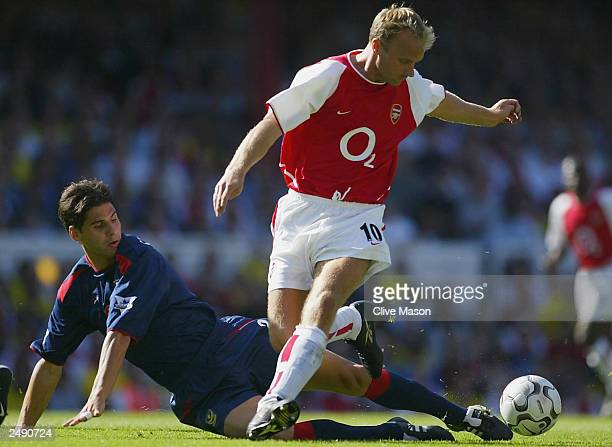 Dejan Stefanovic of Portsmouth challenges Dennis Bergkamp of Arsenal during the FA Barclaycard Premiership match between Arsenal and Portsmouth at...
