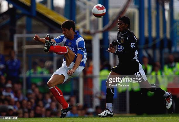 Dejan Stefanovic of Portsmouth chips the ball past Louis Antonio Valencial of Wigan during the Barclays Premiership match between Portsmouth and...