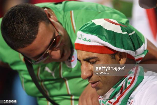A dejected Algeria fan is consoled by a friend after defeat and elimination during the 2010 FIFA World Cup South Africa Group C match between USA and...
