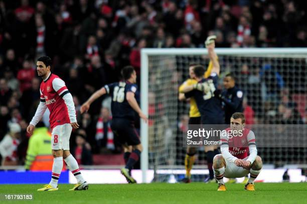 Dejected Arsenal players Mikel Arteta and Jack Wilshere look on as Blackburn players celebrate their team's 1-0 victory during the FA Cup with...
