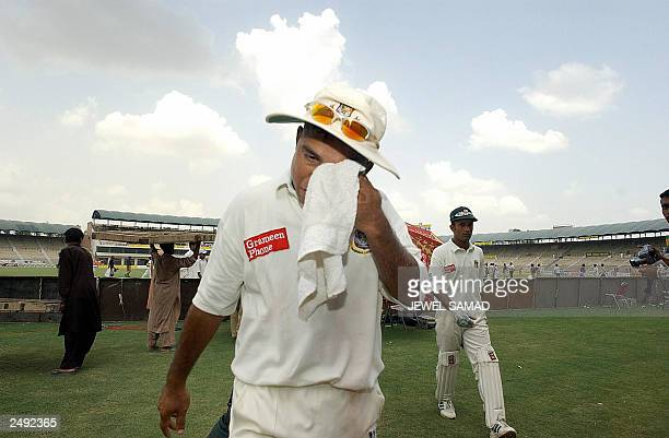 Dejected Bangladeshi cricket team skipper Khaled Mashud wipes his eyes as he is followed by team wicketkeeper Khaled Mahsud after their loss in the...