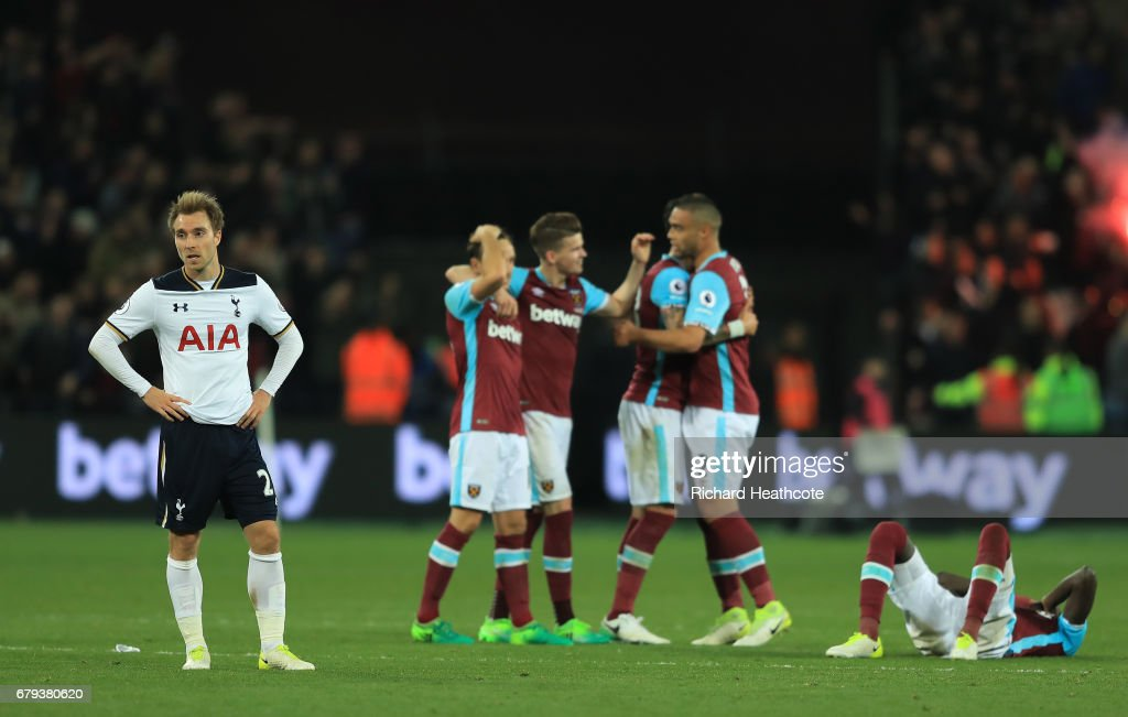 A dejected Christian Eriksen of Tottenham Hotspur looks on as West Ham players celebrate their team's 1-0 victory during the Premier League match between West Ham United and Tottenham Hotspur at the London Stadium on May 5, 2017 in Stratford, England.