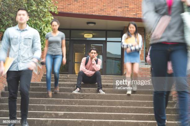 Dejected college student sits alone on stairs