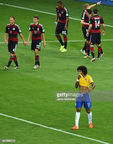 A dejected Dante of Brazil reacts as Andre Schuerrle of Germany celebrates scoring his team's seventh goal with teammates during the 2014 FIFA World...