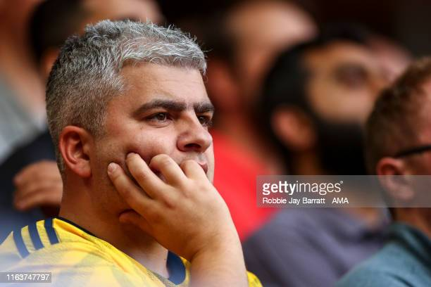 A dejected fan of Arsenal looks on during the Premier League match between Liverpool FC and Arsenal FC at Anfield on August 24 2019 in Liverpool...
