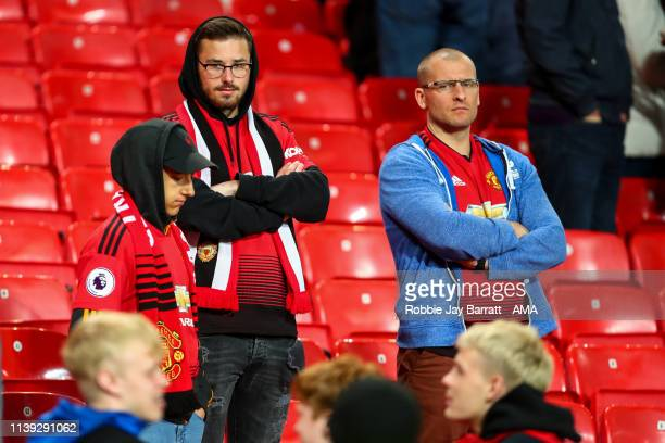 Dejected fans of Manchester United look on at full time during the Premier League match between Manchester United and Manchester City at Old Trafford...