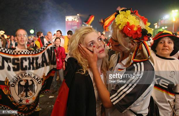 Dejected Germany fans react to their team's loss at a public viewing at the Fan Mile in front of the Brandenburg Gate after watching the UEFA EURO...