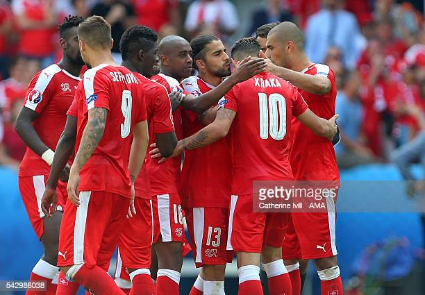 A dejected Granit Xhaka of Switzerland is consoled by his team mates after he misses his penalty during the UEFA EURO 2016 Round of 16 match between...